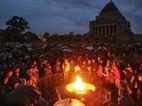 People gather at the Eternal Flame at the Shrine of Remembrance for the Anzac Day dawn service in 2017